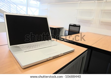 Empty office with new modern office furniture, including desks, cupboards, filing cabinets and chairs. With a notebook computer on the desk. HDR type image - stock photo