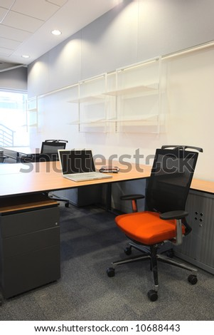 Empty office with new modern office furniture, including desks, cupboards, filing cabinets and chairs. With a notebook computer on the desk. HDR type image