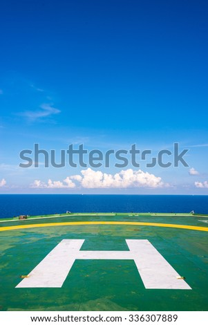 Empty oil rig helipad with few cloud and blue sky, H sign at center in vertical in Gulf of Thailand - stock photo