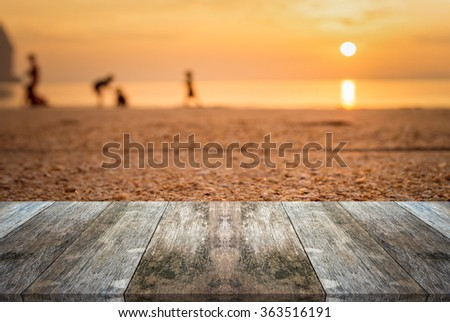 Empty old wooden table or shelf wall and view of sunset or sunrise on sand beach background, For present your products. - stock photo