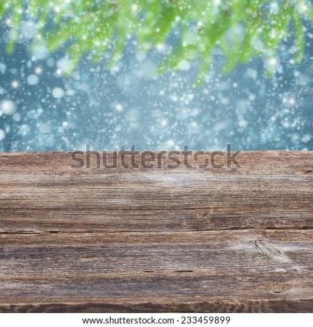 empty old wooden table with snowfall and fir tree bokeh background - stock photo