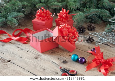 empty open Christmas gift box in the branches of a Christmas tree with Christmas toys on a wooden table closeup. Copy space. Free space for text - stock photo