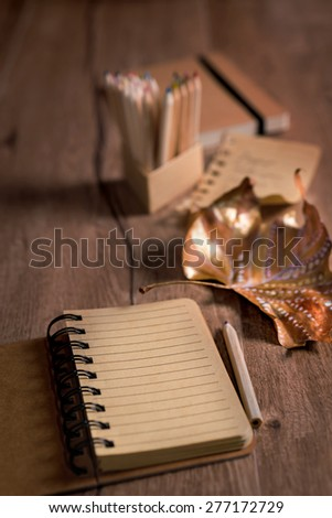 Empty open notebook on a table with pencils and decorated Autumn leaf. Shallow DOF, focus on the blank page. Space for your text on the page and caption above if necessary - stock photo