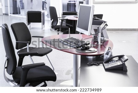 Empty open-plan office with desks chairs computers - stock photo
