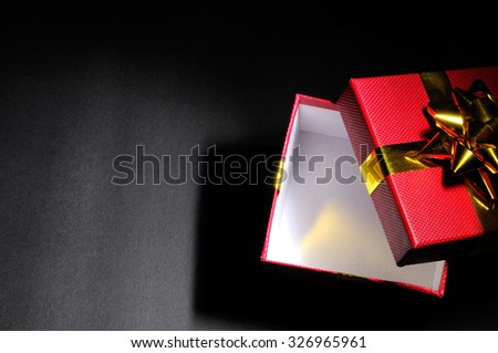 Empty open red gift box with gold bow dim. Horizontal composition. Top view. - stock photo