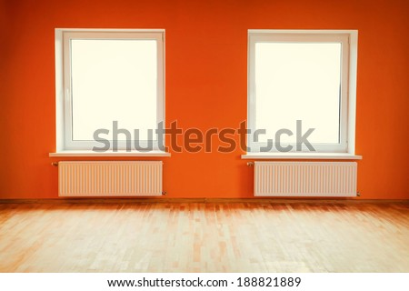 Empty orange room with two windows - stock photo