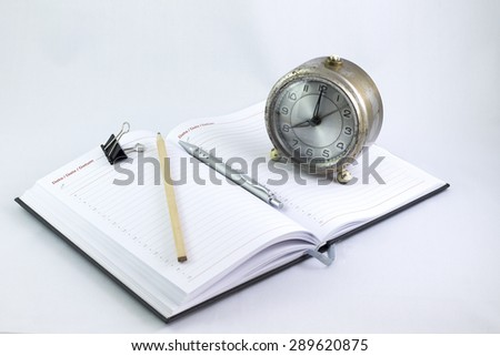 Empty organizer with a pen and paperclips next to a vintage oldfashioned clock - stock photo