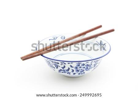 Empty oriental round bowl with wooden chopsticks - stock photo