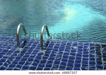 Empty outdoor blue swimming pool with metal silver steps leading into the cool water - stock photo