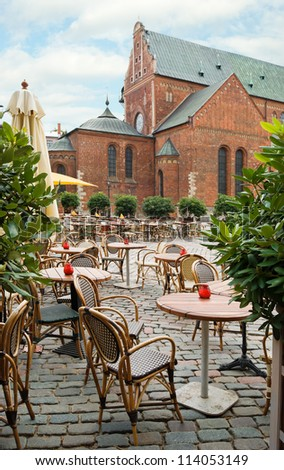 Empty outdoor cafe on the background of the Dome Cathedral in Riga, Latvia - stock photo