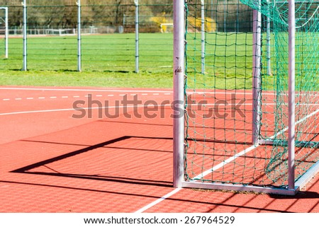 Empty outdoor handball goal with soccer field in the background - stock photo