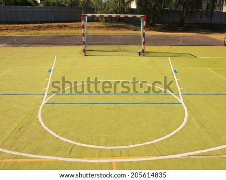 Empty outdoor handball playground, plastic light green surface on ground and white blue bounds lines. - stock photo