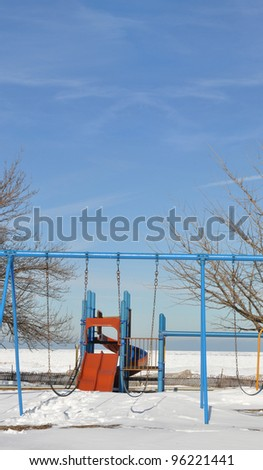 Empty Outdoor Playground Equipment Swings and Slide Sunny Snow Winter Scene Blue Sky Day on north side of Chicago Illinois along Lake Michigan - stock photo