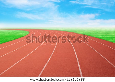 empty outdoor running track with green grass and blue sky