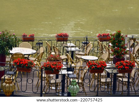 Empty outdoor summer cafe tables and chairs near the river in Paris - stock photo