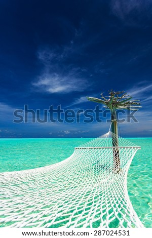 Empty over-water hammock in the middle of tropical lagoon in Maldives - stock photo