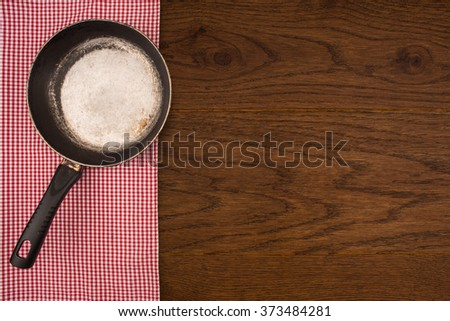 Empty pan on wooden deck table with tablecloth. Flat mock up for design. Top view. - stock photo