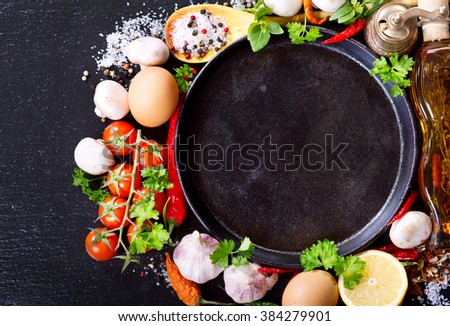 empty pan with various products for cooking on dark board - stock photo