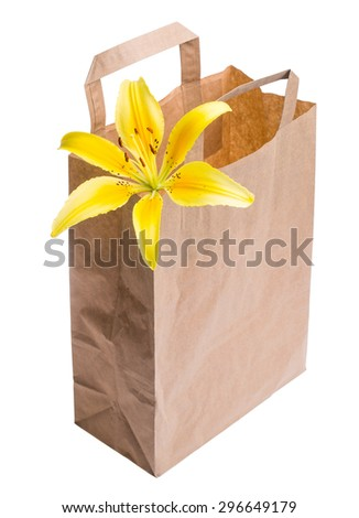 empty paper bag with yellow lily blossom from the store is isolated on a white background - macro lens shot - stock photo