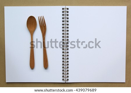 Empty paper for recipe with wooden cooking utensils on kitchen table. - stock photo