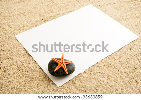 Empty paper sheet on a sand with small detail of sea-star on a stone. - stock photo