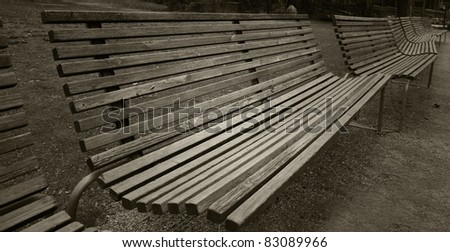 Empty park benches in a row. - stock photo