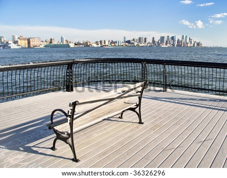 Empty park seat overlooking NYC midtown cityscape, on a bright sunny day. - stock photo