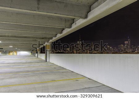 Empty parking garage at night with city panorama - stock photo