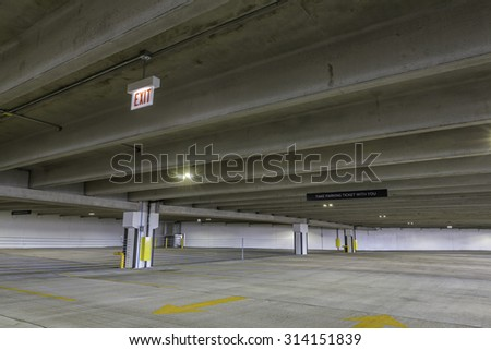 Empty parking garage with exit sign - stock photo