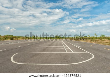 Empty parking lot against a beautiful blue sky - stock photo