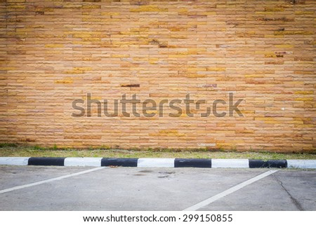 Empty parking lot with brown sandstone wall.