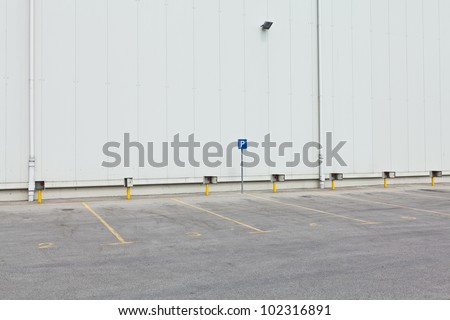 Empty parking lot with enumerated parking spots and parking sign in front of white wall - stock photo