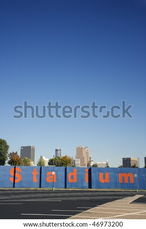 Empty parking stalls in front of a sign reading 'stadium'. The tops of trees and downtown buildings can be seen in the background. Vertical shot. - stock photo