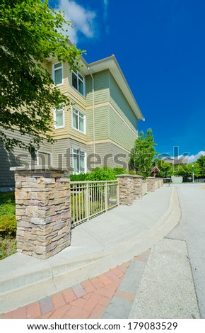 Empty pedestrian sidewalk with townhouse, condo at the back. Vertical. - stock photo