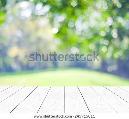 Empty perspective white wood over blurred trees with bokeh background, for product display montage - stock photo