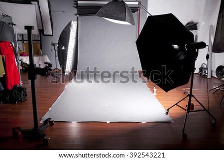 Empty photo studio with lighting equipment, Dark studio with grey background - stock photo