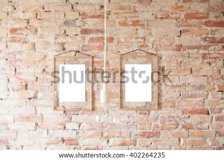 Empty picture in wooden frame where you can write your text, hanging on brick wall - stock photo