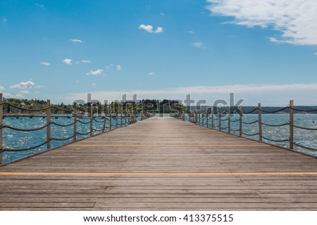 Empty pier in a peaceful sea harbor on a background of blue sky. - stock photo