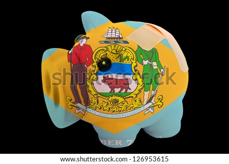 empty piggy rich bank in colors of flag of us state of delaware on black background - stock photo