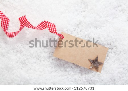 Empty place card or gift card for christmas and festive winter concepts. On white snow background. - stock photo
