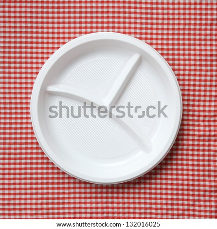 Empty plastic plate on a checkered cloth. - stock photo