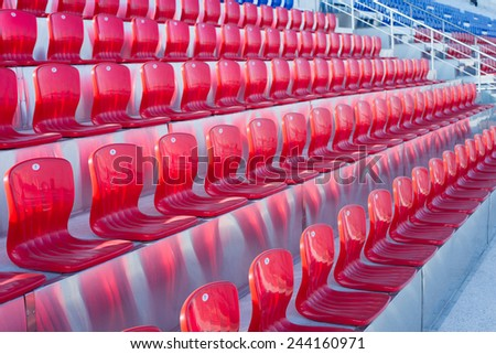 Empty Plastic Red Chairs at the Stadium - stock photo