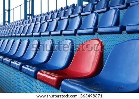 Empty plastic seats at stadium, open door sports arena.  - stock photo