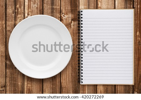 Empty plate and cookbook on table - stock photo