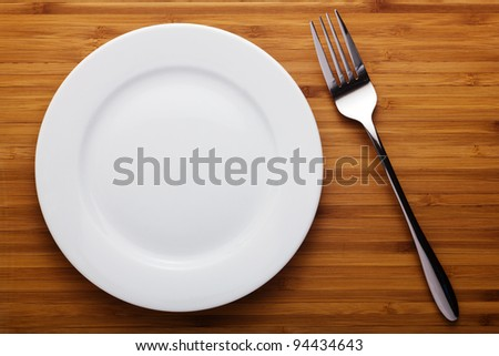 Empty plate and fork on wood table - stock photo