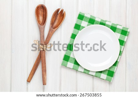 Empty plate and kitchen utensils over wooden table background. View from above with copy space - stock photo