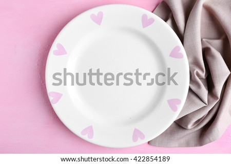 Empty plate and napkin on pink background - stock photo