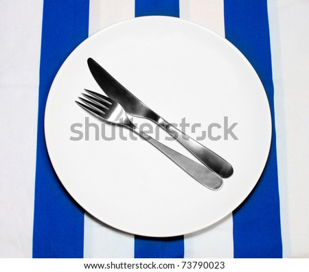 Empty Plate And Silverware on tablecloth in greek colors - stock photo