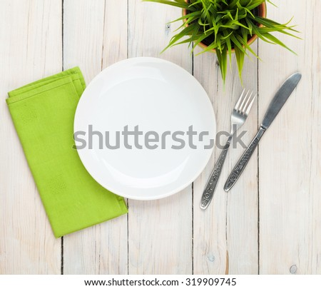 Empty plate and silverware over white wooden table background. View from above with copy space - stock photo