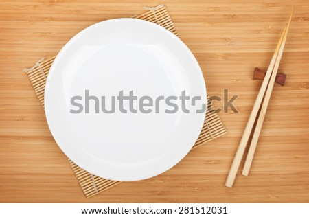 Empty plate and sushi chopsticks on bamboo table - stock photo
